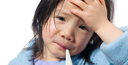 Ill child with a thermometer in her mouth. She is holding her forehead.